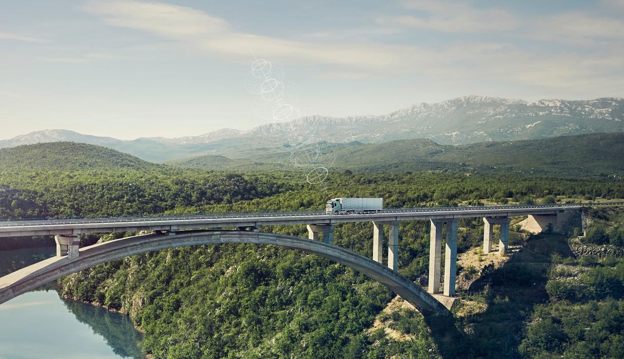"""Prijungtas """"Volvo"""" sunkvežimis važiuoja per tiltą atokioje vietovėje"""