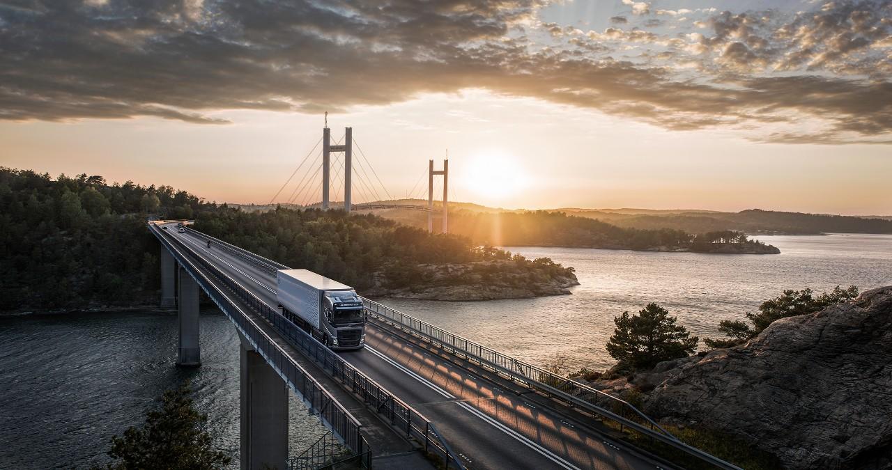"""""""Volvo"""" sunkvežimis važiuoja tiltu virš vandens, už jo leidžiantis saulei"""