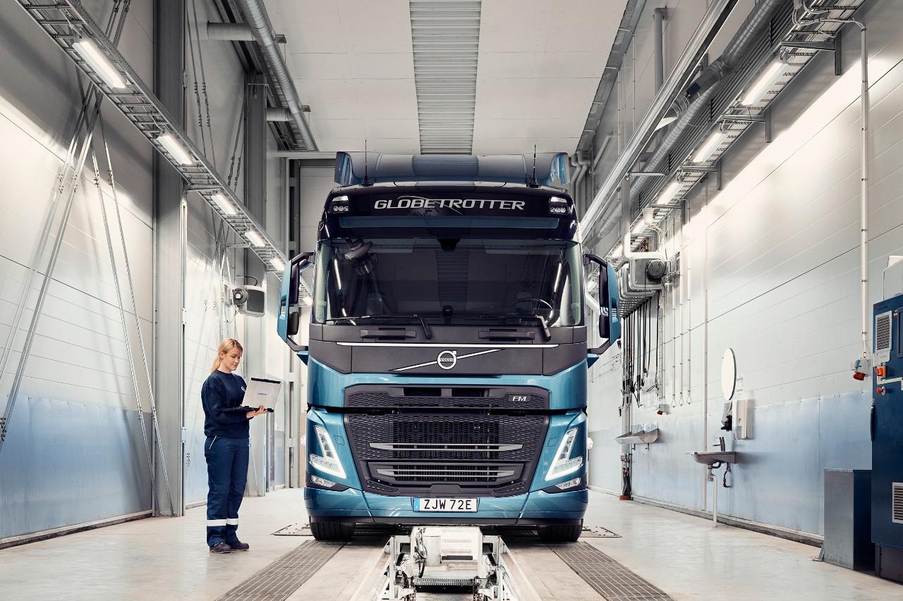 """""""Volvo"""" techninės priežiūros specialistas stovi šalia sunkvežimio ir laiko kompiuterį"""