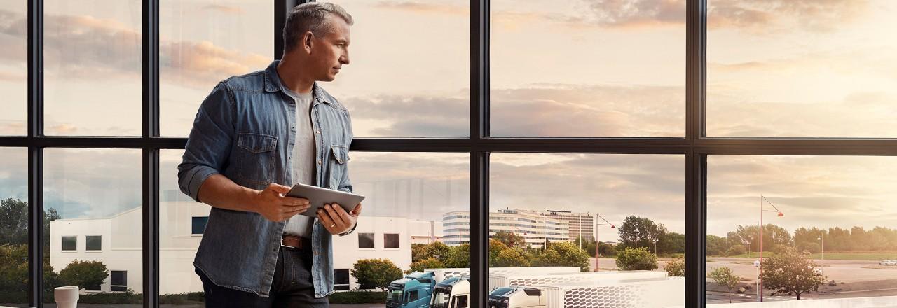 Planšetinį kompiuterį laikantis vyras stovi prie lango ir žvelgia žemyn į savo sunkvežimių parką