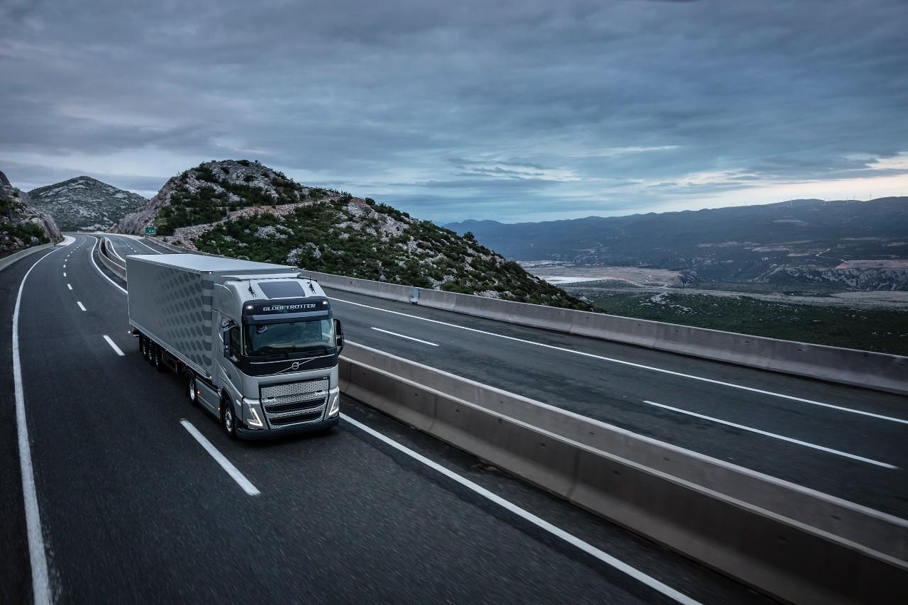 Sunkvežimis važiuoja per tiltą, kurio fone matyti kalnai