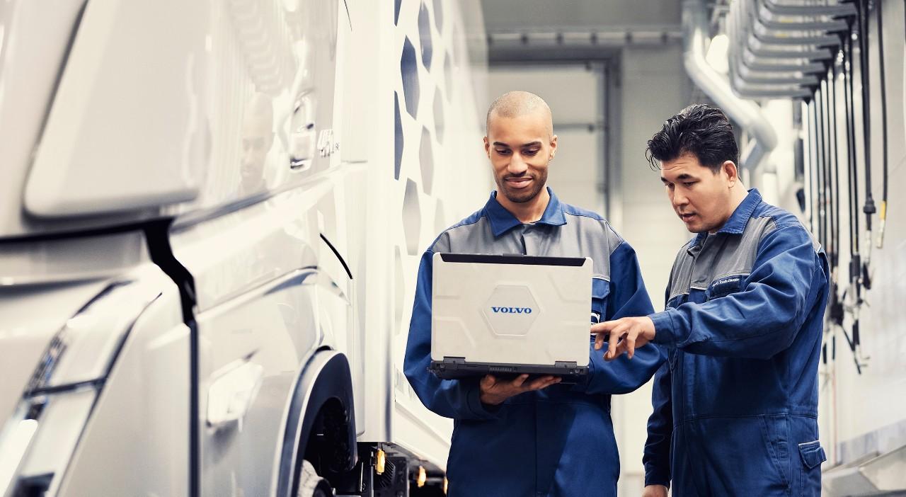 """Du """"Volvo"""" techninės priežiūros specialistai stovi šalia sunkvežimio ir žiūri į nešiojamąjį kompiuterį"""